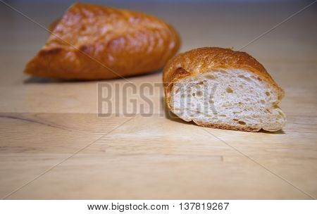 cutting french bread baguette on wood background