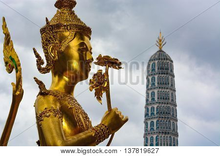 Golden kinnara statue at the historic Grand Palace in Bangkok, Thailand