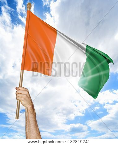 Person's hand holding the Ivory Coast national flag and waving it in the sky, 3D rendering