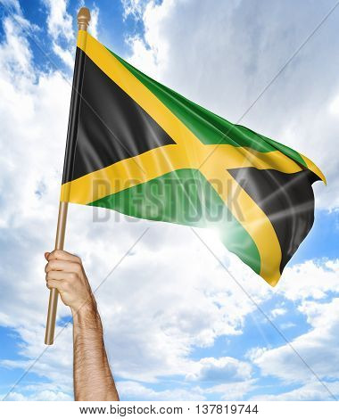 Person's hand holding the Jamaican national flag and waving it in the sky, 3D rendering