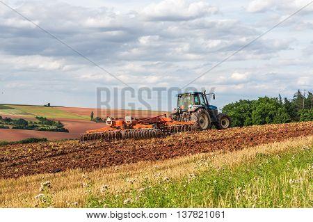 Farmer In Tractor Working On A Field