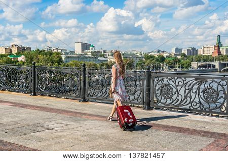 Young lady walking and carrying a suitcase in Moscow not far from Kremlin Russia