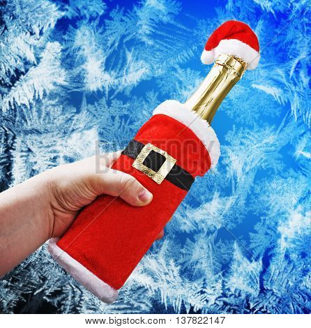 hand holding a champagne bottle in a Christmas decoration santa clothes on a Ice Background