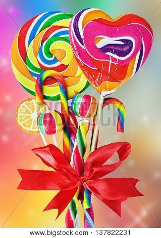 colored sweets with red ribbon bow on a colored background