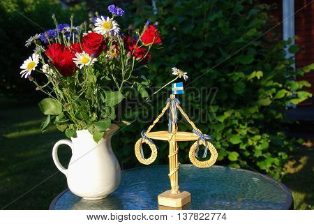 Summer flowers and midsummer decoration on a table in a garden
