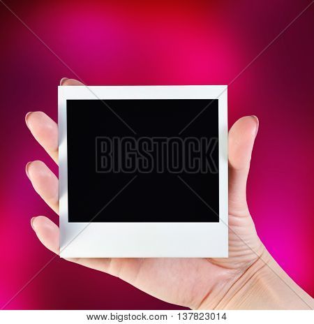 picture frame in her hand on a colorful red background