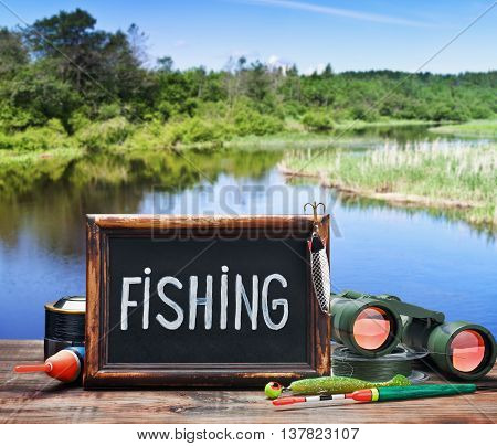 fishing tackle and a blackboard on a background of lake