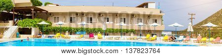 BALI GREECE - APRIL 29 2016: Relax and sunbathe by pool with clear blue water in Resort hotel Atali Village 4 star. Tourists in swimming trunks and swimwear have a rest by the pool in middle of day. Bali Rethymno Crete Greece