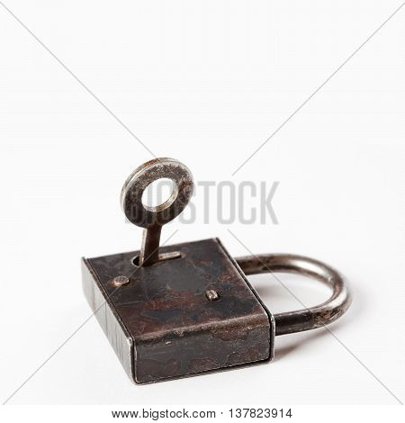 Old style padlock with key in hole. hanging lock close-up. texture and detailed. white background
