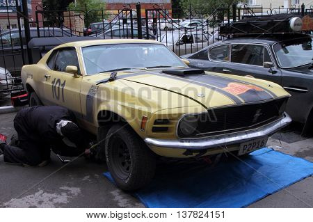 PERM RUSSIA - JUNE 29 2016: Rally of retro-cars Peking-Paris 2016 June 29 2016 in Perm Russia. Participant rally Ford Mustang repairs.