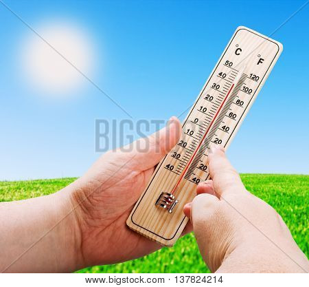 wooden thermometer in hand on a background of a bright sun