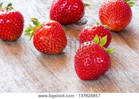 Close-up view of red strawberry on wooden floor