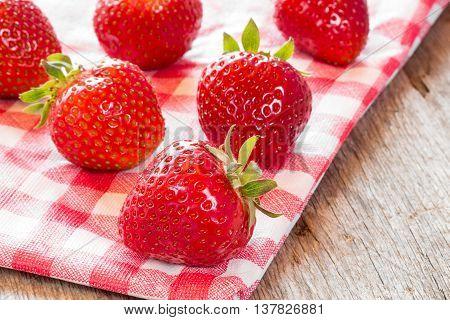 Fresh strawberries on red and white checkered napkin.