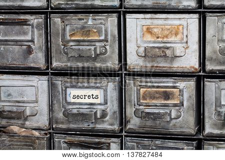Secrets concept image. Closed archive storage, filing cabinet interior. aged silver metallic boxes with index cards. library service information security