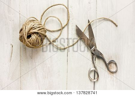 A photo of vintage scissors and a roll of twine shot from above on light wooden boards background texture with copyspace; craft concept