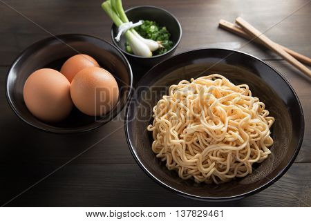 Instant noodles in Ceramic cop and eggs side dishes on Dining table