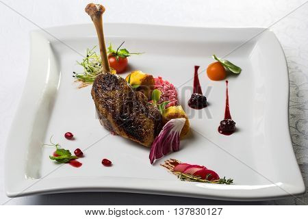 Confit duck or goose leg crisp delicious served with garnish colorful tomatoes vegetables and blackberry sauce on white background