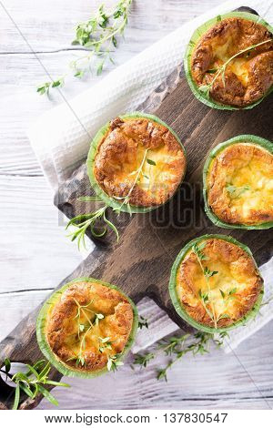Savory cheddar cheese and leek mini quiches with thyme on dark wooden cutting board. Top view