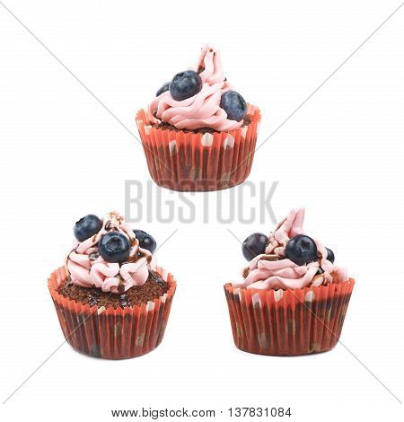 Single chocolate muffin coated with the pink cream frosting and fresh bilberries, composition isolated over the white background, set of three different foreshortenings