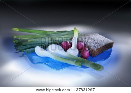Slice of rye bread and green goods on a blue saucer. Light brush