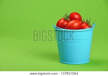 Blue Bucket Of Red Cherry Tomatoes Over Green