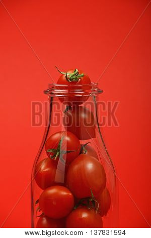 Cherry Tomatoes In Glass Bottle Over Red