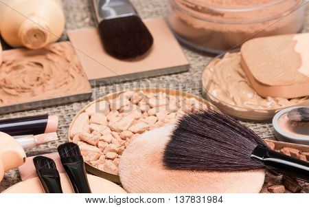 Makeup products to create the perfect complexion. Correctors, foundation, powder, bronzer with brushes and cosmetic sponges on sackcloth. Side view, shallow depth of field