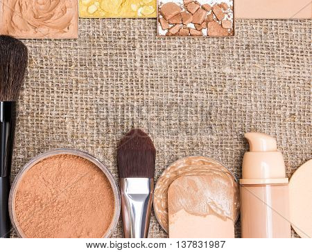 Beauty background. Cream-to-powder and liquid foundation, crushed bronzing and shimmer powder golden color, compact and loose powder with makeup brushes and cosmetic sponges on sackcloth