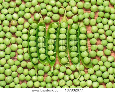 Fresh green peas texture vegetable. Pea pod with leaves on wooden background. Organic food