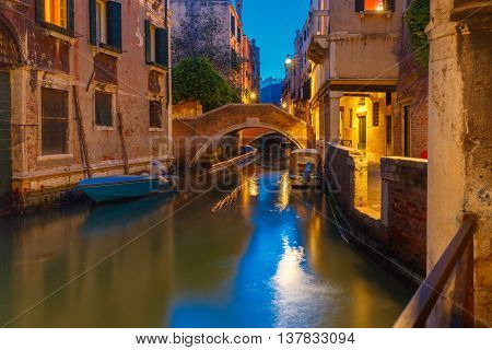Lateral canal and pedestrian bridge in Venice at night with street light illuminating bridge and houses, with docked boats, Italy