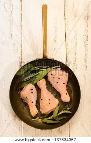 raw chicken drumstick with sage peppercorn and coarse salt in a brass pan
