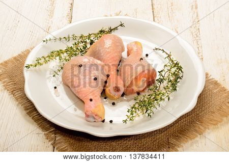 raw chicken drumstick with thyme peppercorn and coarse salt on a plate
