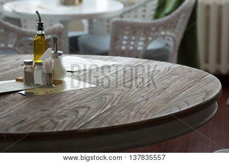 Restaurant interior. Pepper, salt olive oil sugar napkins and toothpicks on the table.
