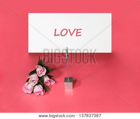 A note holder with a roses and a card with the word love on rose background