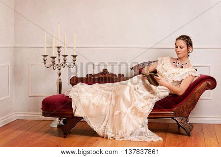 portrait of Victorian woman reading book on fainting couch