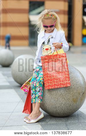 Young little girl with full shopping bags standing near boutique. Girl is Looking Into Shopping Bag. Portrait of a kid with shopping bags. Blond girl in sunglasses.