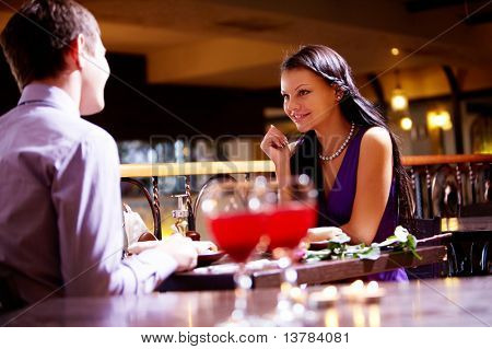 Photo of couple sitting at the table in restaurant