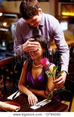 Handsome man shuts woman's eyes by hand and gives rose