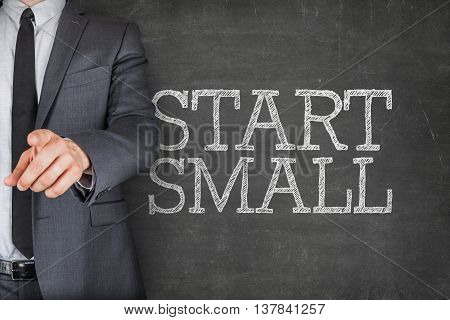 Start small text on blackboard with businessman finger pointing