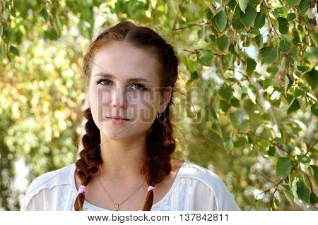Beautiful girl of Slavic appearance against a birch