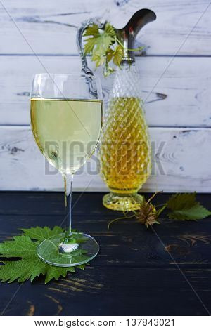 White wine in glass and antique wine pitcher made from silver and chrystal glass on wooden background