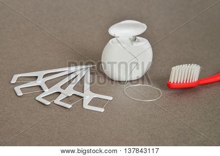 Dental Hygiene Tool Set: dental floss and toothbrush.
