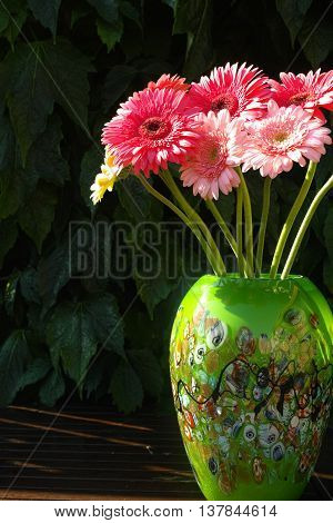 Colorful gerbera daisies in green vase made from mozaic murano glass