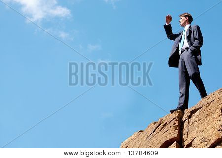 Photo of happy businessman standing on the cliff and looking into the distance on the background of bright sky