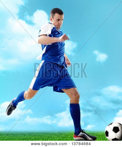 Portrait of a soccer player with ball on a blue background