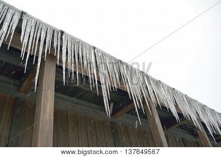 Icicles on a roof edge in snowy weather.