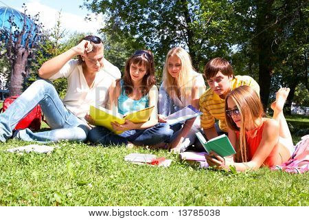Portrait of smart friends reading books in park together