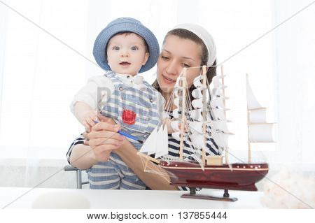 Travel Concept. Mother And Her Child Boy Making Model Ship.