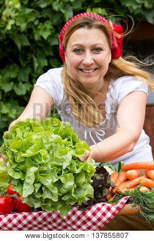A smiling market woman offering fresh salad to