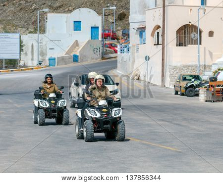 Santorini, Greece - May 2, 2016: Girls tourists on quad bikes ride along the embankment in the port Athinios. The Greek islands are one of the most visited tourist destinations in Europe.